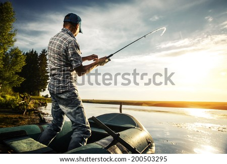 Mature man fishing from the boat on the pond at sunset Royalty-Free Stock Photo #200503295
