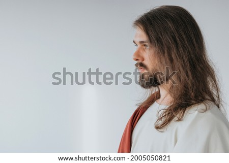 Picture of Jesus Christ wearing white and red robes standing on a white backrgound