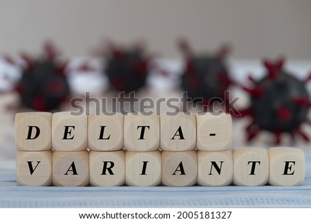 wooden cubes with the german word for Delta-Variante, concept for the corona spreading of delta virus variant, virus model in the background