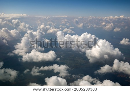 Aerial view from airplane window of white puffy clouds on bright sunny day. Royalty-Free Stock Photo #2005239383