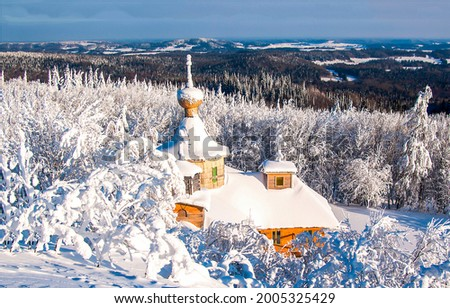 Wooden church in the winter snow forest. Church in snowy forest in winter. Wooden church in winter snow forest Royalty-Free Stock Photo #2005325429