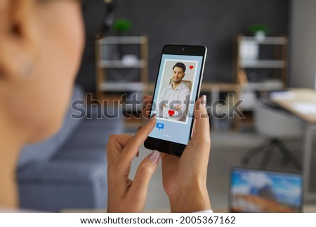 Finding love online using dating websites or mobile apps: Woman who's looking at profile pics with red hearts and message buttons on phone display gives a like to handsome young man. Closeup, close up