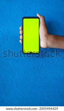 Boy hand showing mobile smartphone screen in milk green Color with Isolated on blue background. Mobile phone screen on blue background with space for text.