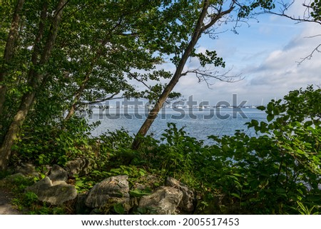 A scenic framed view of the Sandy Hook Bay from the Henry Hudson Trail in Atlantic Highlands. Royalty-Free Stock Photo #2005517453