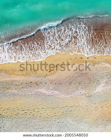 Human and dog footprints on a sandy shore along the sea with breaking waves, aerial vertical shot directly above Royalty-Free Stock Photo #2005548050