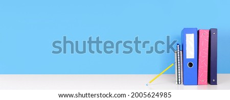 School binders, notebooks and pencil on a white shelf against a blue banner background. Back to school concept. Copy space. Royalty-Free Stock Photo #2005624985