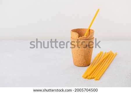 Waffle coffee cups and pasta straws on neutral background with copy space. Zero waste, plastic free, stop pollution, ecological concept Royalty-Free Stock Photo #2005704500