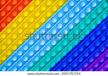 Bright, popular texture. Colorful fashion anti-stress touch toys fidget push pop it. Autism. Royalty-Free Stock Photo #2005787294
