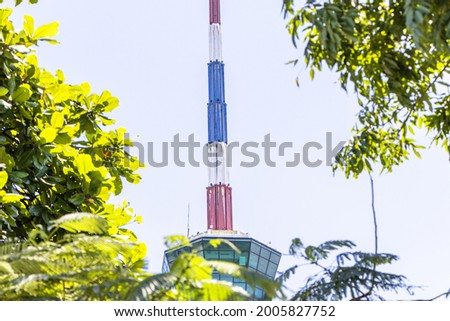 Close-up photo Lighthouse and traffic control tower cargo ship sailing as national flag picture with green tree blur pictures in front blue sky clouds a background. symbol landmark port of Lamchabang