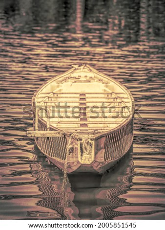 Abstract vintage picture with a golden boat floating on the water