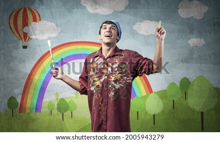 Young male artist with paintbrush. Happy painter in shirt and bandana standing on background colorful picture on wall. Summer landscape with hot air balloon and rainbow. Creative hobby and profession