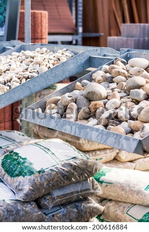 Stock at a nursery or landscaping business with weathered smooth stones in assorted shapes and sizes in metal bins with stacked sacks of potting soil and fertiliser #200616884