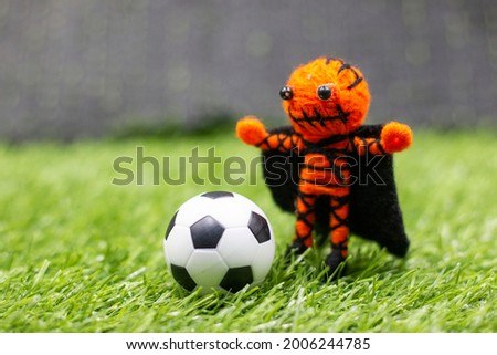 Soccer ball with ghost are on green grass for Halloween Day