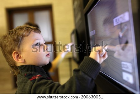 Child using interactive touch screen in a museum Royalty-Free Stock Photo #200630051