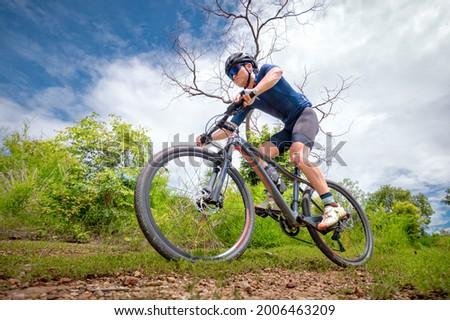 Mountain bikers ride MTB, mountain bike downhill to the extreme. Asian man rides MTB, mountain bike downhill in the wild to extremes. Extreme Sport and MTB, mountain bike downhill Concept. Royalty-Free Stock Photo #2006463209