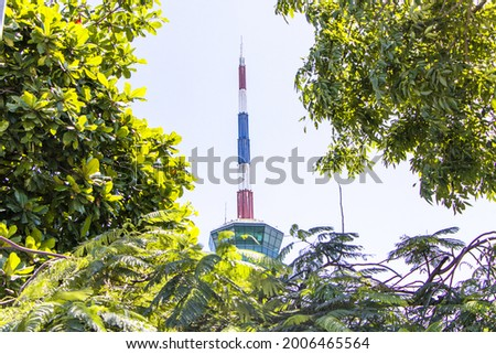 Close-up photo Lighthouse and traffic control towersymbol landmark port of Lamchabang. Cargo ship sailing as national flag picture with green tree blur pictures in front blue sky clouds a background.