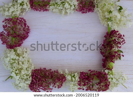 On a wooden background lies a picture frame , pink and white hydrangea flowers.