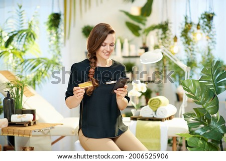 happy 40 years old woman worker with smartphone and credit card buying online in modern beauty studio.