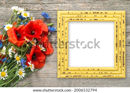 Poppy flowers bouquet and picture frame on rustic wooden background