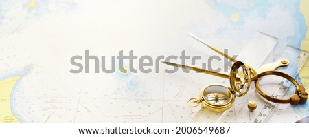 """Retro styled golden compass (sundial), antique vintage W HC 6"""" brass dividers calipers nautical navigation chart tool, parallel ruler, old white map close-up.   Royalty-Free Stock Photo #2006549687"""