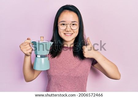 Young chinese girl holding italian coffee maker smiling happy and positive, thumb up doing excellent and approval sign