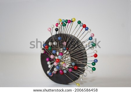 colorful pins on ring magnet white background, magnetic pin needle cushion, tailor, sewing, fashion, design materials equipments, tools, cloth fastening fabric, glass headed pin
