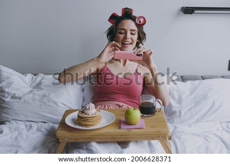 Young happy woman 20s in pajamas hair curlers lie in bed wrap covered blanket duvet take picture shot of breakfast on tray on mobile cell phone rest relax at home Good mood morning bedtime concept.