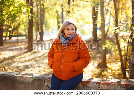 Delighted female in outerwear smiling and covering eye with dry leaf on sunny weekend day in autumn park Royalty-Free Stock Photo #2006680370