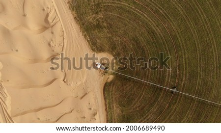 AERIAL. Circular green irrigation patches for agriculture in the desert. Dubai, UAE. Royalty-Free Stock Photo #2006689490