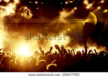 silhouettes of concert crowd in front of bright stage lights #200677982