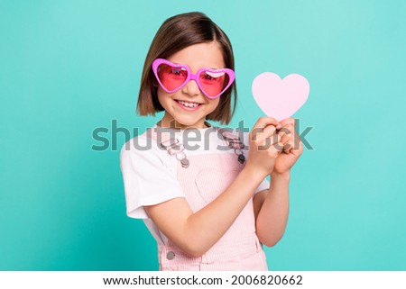 Photo of funny adorable school girl wear pink overall glasses smiling holding little heart isolated teal color background Royalty-Free Stock Photo #2006820662