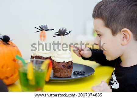 Boy eats sweets on Halloween party. Toddler caucasian boy eats Halloween muffins or cupcakes with white cream and spiders decorations. Tasty and scary food on Halloween party