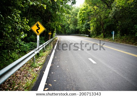 Yellow warning sign winding road with nature