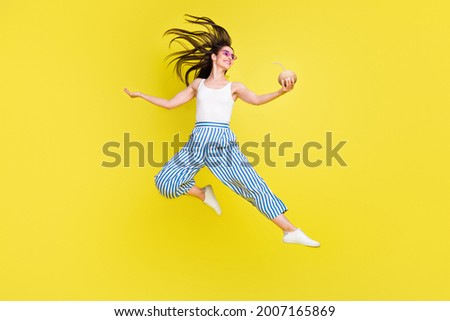 Full body photo of funny brunette millennial lady jump hold coconut wear top pants sneakers spactacles isolated on yellow color background