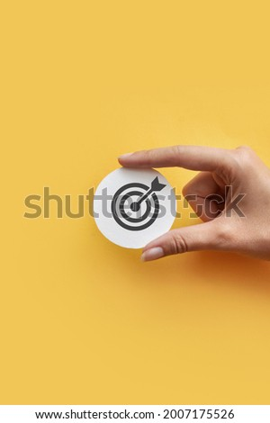 A paper circle with a picture of a target. A symbol of achieving the goal and success