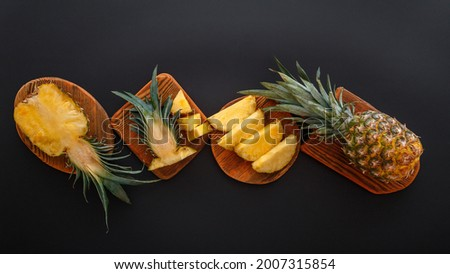 Sliced pineapple in different shapes. Ripe pineapple on cutting board cooking summer dessert on black background. Flat lay. Long web banner. High quality stock photo