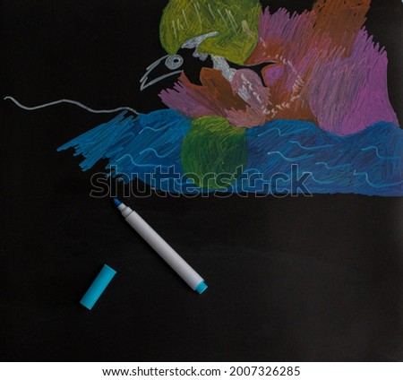 Kids picture on blackboard and board markers. Back to school concept.