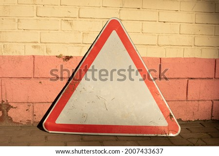 The road sign stands against the wall. The triangle symbolizes traffic. Special symbol for the driver.
