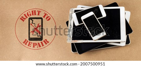 right to repair symbol next to broken tablets and smart phones on board consumer right to repair goods Royalty-Free Stock Photo #2007500951