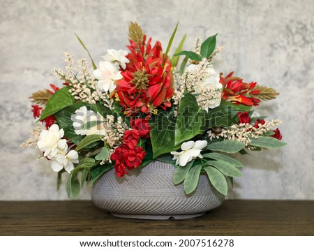 A handmade silk flower center piece arrangement with red and ivory flowers and green filler leaves. Royalty-Free Stock Photo #2007516278