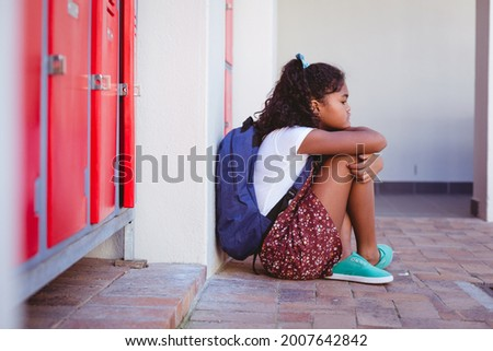Unhappy african american schoolgirl sitting by lockers in school corridor with schoolbag. childhood and education at elementary school. Royalty-Free Stock Photo #2007642842