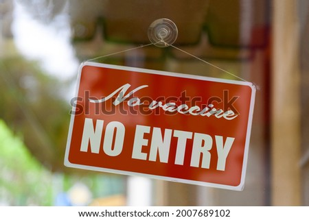 Close-up on a red sign in the window of a shop displaying the message: No vaccine, no entry .