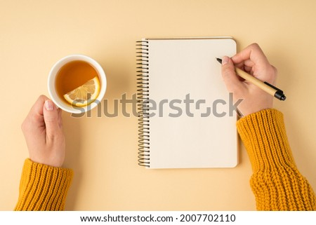 First person top view photo of female hands in yellow pullover writing in spiral planner and holding white cup of tea with lemon slice on isolated pastel orange background with copyspace