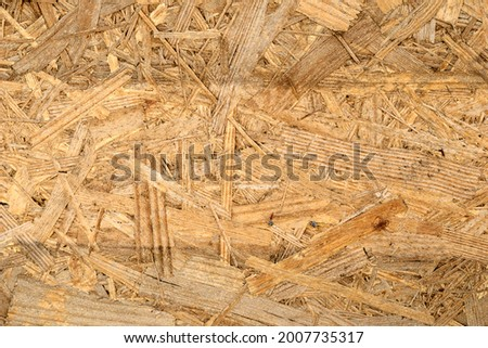 OSB board texture. Brown wooden background. Simple pressed chipboard pattern. Chip board background. Brown wood texture. High quality photo Royalty-Free Stock Photo #2007735317