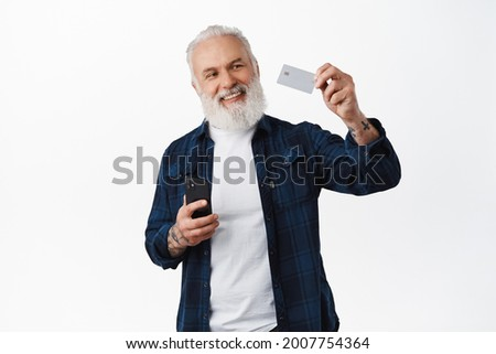 Happy senior man holding smartphone, raising hand and showing credit card with satisfied smile, nod in approval, recommend online payment, mobile banking app, standing over white background