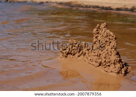 sand castle on the beach near the water. High quality photo Royalty-Free Stock Photo #2007879356