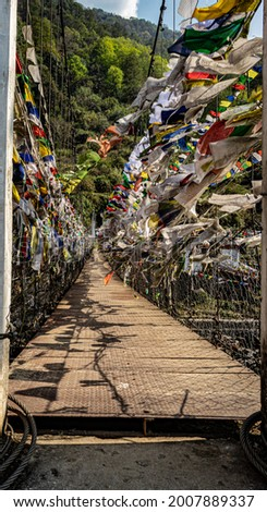 suspension iron bridge with many buddhist holy flags from unique perspective image is taken at chaksam bridge tawang arunachal pradesh india.