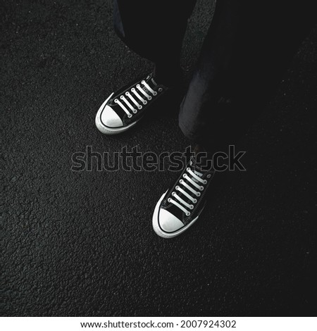 Top view of a young man's feet wearing sneakers, black and white photography.