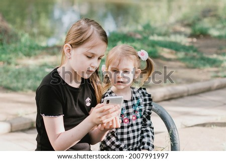 Two girls sitting on bench in spring summer park and watching cartoons on smartphone. Wireless technologies concept. Children addiction from gadgets.