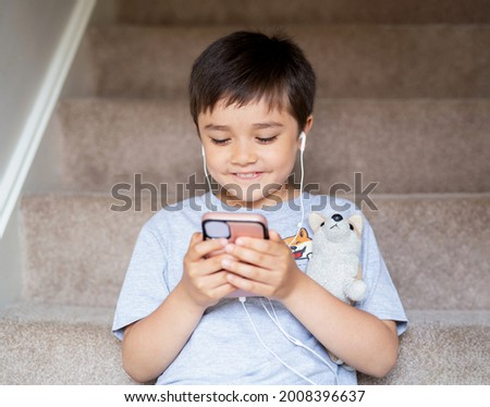 Candid shot child sitting on staircase wearing earphones listening relaxing music at home.Portrait happy boy playing games on mobile phone, Kid watching cartoon on cell phone.Children and Technology